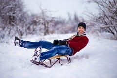 Hombre joven alegre que se divierte en un trineo en invierno Fotos de archivo