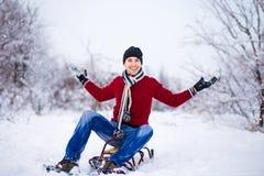 Hombre joven alegre que se divierte en un trineo en invierno Imagen de archivo