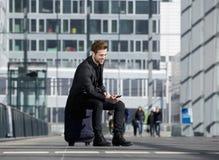 Hombre joven alegre que se sienta en la maleta que mira el teléfono móvil Foto de archivo libre de regalías