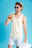 Hombre joven alegre que sostiene un bolso más fresco y que bebe la cerveza Fotografía de archivo