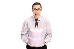 Hombre joven alegre que sostiene una torta de cumpleaños Foto de archivo