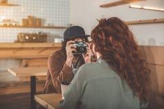 Hombre joven alegre que toma la foto de la mujer dentro Fotografía de archivo