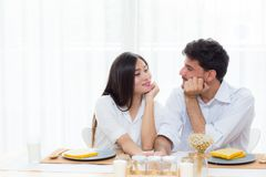 Hombre joven alegre y mujer asiáticos que almuerzan que se sienta y que hablan junto Imagen de archivo libre de regalías