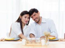 Hombre joven alegre y mujer asiáticos que almuerzan que se sienta y que hablan junto Imagen de archivo