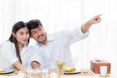 Hombre joven alegre y mujer asiáticos que almuerzan que se sienta y que hablan junto señalando algo Foto de archivo