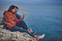 Hombre joven alegre y mujer que toman las fotos en la playa Imagen de archivo libre de regalías