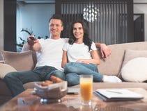 Hombre joven alegre y mujer que ven la TV junto Imágenes de archivo libres de regalías