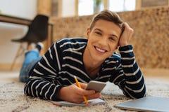 Hombre joven alerta que miente en el piso con su teléfono imagen de archivo libre de regalías