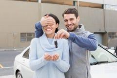 Hombre joven alrededor para sorprender a la novia con el nuevo coche Imágenes de archivo libres de regalías