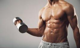 Hombre joven apto que ejercita con pesas de gimnasia Fotografía de archivo libre de regalías