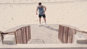 Hombre joven apto que ejercita en los pasos en la playa metrajes