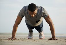Hombre joven apto que hace pectorales en la playa Fotos de archivo