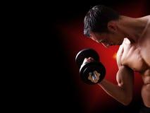 Hombre joven apto que se resuelve con pesa de gimnasia Imagen de archivo