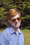 Hombre joven apuesto con el pelo y las sombras rojos fotografía de archivo libre de regalías