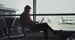 Hombre joven apuesto en el aeropuerto que hablaba en su teléfono en lo mismo él cerró su cuaderno y va a conseguir almacen de video