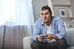 Hombre joven asentado en un sofá que juega a los videojuegos dentro de su sitio Fotos de archivo