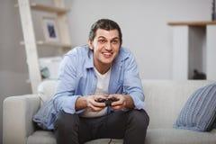 Hombre joven asentado en un sofá que juega a los videojuegos dentro de su sitio Imágenes de archivo libres de regalías