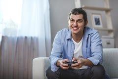 Hombre joven asentado en un sofá que juega a los videojuegos dentro de su sitio Foto de archivo