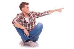 Hombre joven asentado que señala a la cara Fotografía de archivo libre de regalías