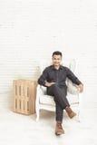 hombre joven asiático casual que mira la cámara mientras que se sienta en los decoros Imagen de archivo