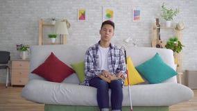 Hombre joven asiático ciego que lee un libro del texto de Braille que se sienta en el sofá en la sala de estar almacen de metraje de vídeo