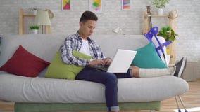 Hombre joven asiático con la pierna quebrada en los vendajes que mienten en el sofá con el ordenador portátil almacen de video