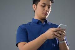 Hombre joven asiático en casual usando el teléfono móvil Fotos de archivo