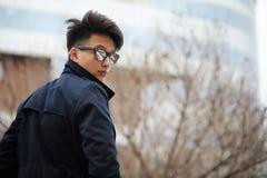 Hombre joven asiático en una capa en la calle Imágenes de archivo libres de regalías
