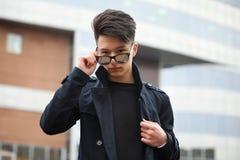 Hombre joven asiático en una capa en la calle Imagenes de archivo