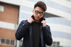 Hombre joven asiático en una capa en la calle Foto de archivo