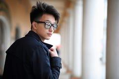 Hombre joven asiático en una capa en la calle Imagen de archivo