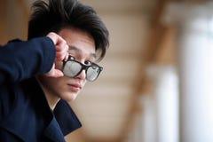 Hombre joven asiático en una capa en la calle Fotos de archivo