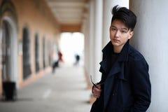 Hombre joven asiático en una capa en la calle Foto de archivo libre de regalías