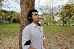 Hombre joven asiático que escucha la música con los auriculares y que inclina un árbol en el parque al aire libre público Fotos de archivo