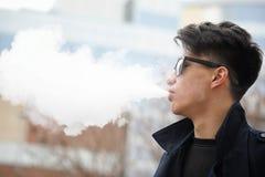 Hombre joven asiático que fuma en la calle Fotografía de archivo