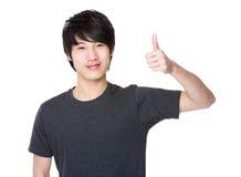Hombre joven asiático que muestra el pulgar para arriba Foto de archivo