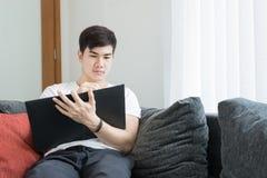 Hombre joven asiático que piensa y que se pregunta mientras que escribe un papel en Fotos de archivo libres de regalías