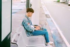 Hombre joven asiático que se sienta en la silla en la parada de autobús del aeropuerto y fotos de archivo