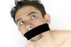 Hombre joven asustado con el vendaje en boca Foto de archivo