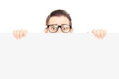 Hombre joven asustado con los vidrios que ocultan detrás de un panel en blanco Fotografía de archivo
