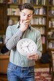 Hombre joven asustado del tiempo que sostiene el reloj imagen de archivo