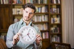 Hombre joven asustado del tiempo que sostiene el reloj fotografía de archivo