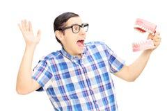 Hombre joven asustado que sostiene una muestra de los dientes hecha fuera de molde de yeso Imagen de archivo