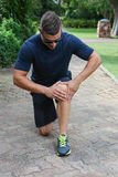 Hombre joven atlético con la rodilla dolorida Fotos de archivo
