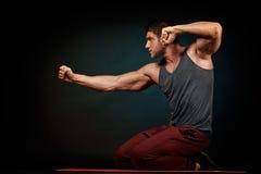 Hombre joven atlético en estudio con el fondo oscuro Imagenes de archivo