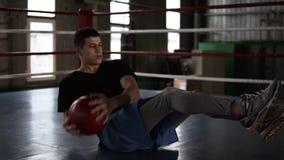 Hombre joven atlético que hace ejercicio del abdomen en el piso en el ring de boxeo Hombre que hace entrenamiento usando una bola almacen de metraje de vídeo
