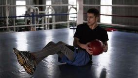 Hombre joven atlético que hace ejercicio del abdomen en el piso en el ring de boxeo Hombre que hace entrenamiento usando una bola metrajes