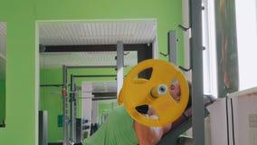 Hombre joven atlético que hace ejercicios con el barbell en el gimnasio, club de fitness almacen de metraje de vídeo