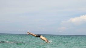 Hombre joven atlético que salta de piedra en el agua azul del mar del océano La aventura muscular se divierte vacaciones de la af almacen de metraje de vídeo