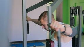 Hombre joven atlético que usa la máquina del ejercicio en el gimnasio almacen de metraje de vídeo